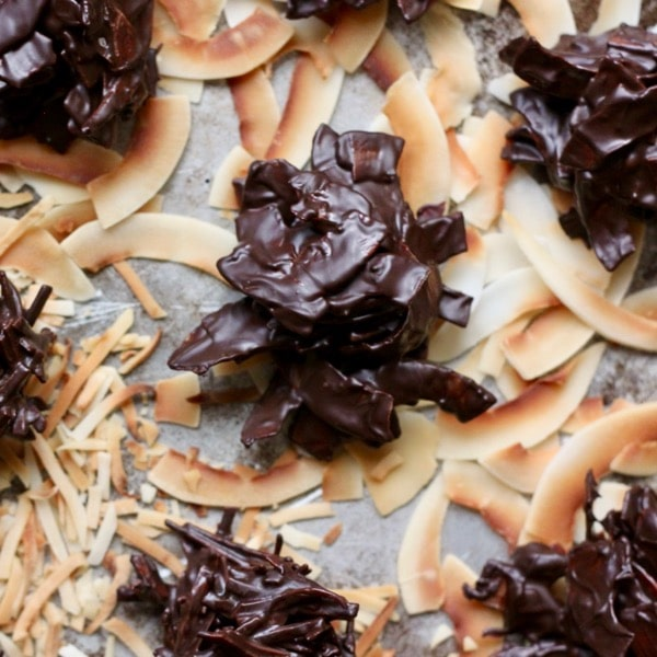 Dark chocolate coconut haystacks sit on top of toasted coconut flakes