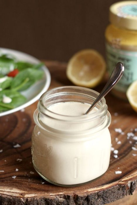 lemon tahini sauce in small container with salad in background