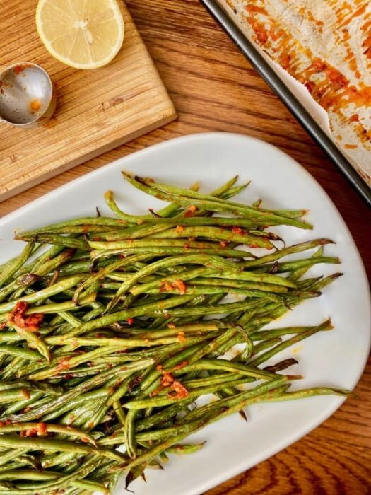 Harissa roasted green beans served on a white serving platter