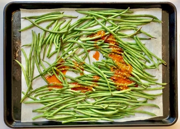 pour harissa sauce over roasted green beans