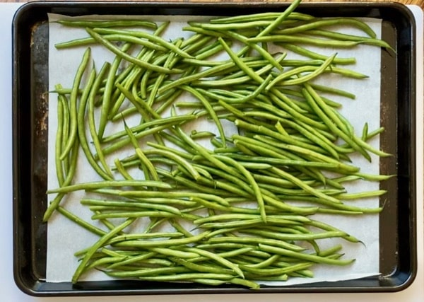 washed green beans on a parchment lined baking sheet