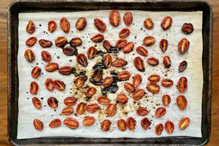 Roasted cherry tomatoes on a parchment lined baking sheet
