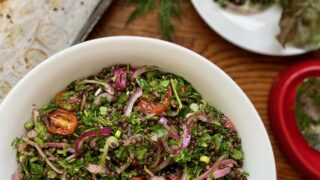 plant-based lentil salad with dill parsley roasted tomatoes and pickled red onions in a white serving bowl