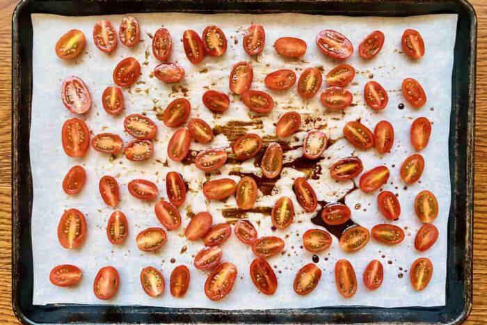 Cherry tomatoes tossed in balsamic vinegar and olive oil on a parchment lined baking sheet
